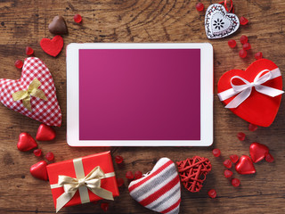 Digital tablet with gifts and hearts on wooden table. View from above. Valentines Day concept