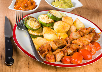 skewered meat and vegetables on wooden plate