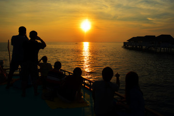 Silhouette of couple lovers and tourist watching the sun setting