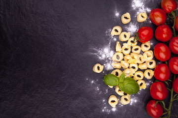 Tortellini and flour on a black stone plate.