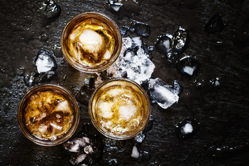 Cold whiskey in a glass with crushed ice on a black stone wet ba