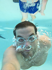 man swimming underwater, view from under the water
