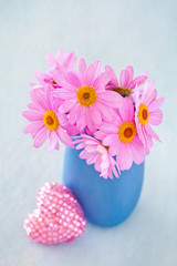 Daisies in a vase decorated with a heart on a blue background .