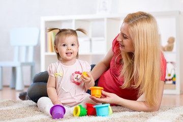 child girl and mother playing together with toys at home
