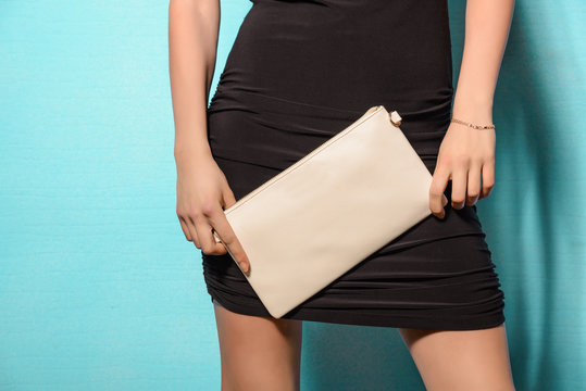 Fashionable woman with a white bag and black evening dress