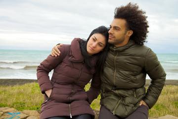 Sad couple hugging in front of ocean in winter feeling bad