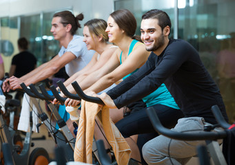 adults riding stationary bicycles in fitness club