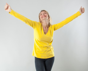 success concept - satisfied 20s blond woman with yellow shirt outstretching her arms for wellbeing or waking up,studio shot