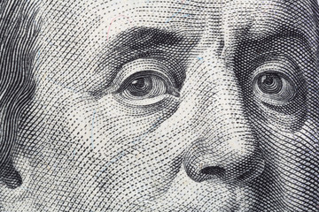 Close view of Benjamin Franklin on the front of a US hundred dollar bill.