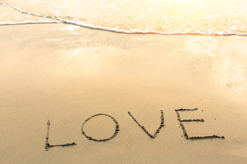 Inscription LOVE on a gentle beach sand with the soft wave.