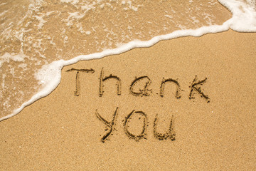 Thank you - Inscription on sand beach with the soft wave.