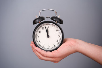 Classic alarm clock in woman hand against grey background