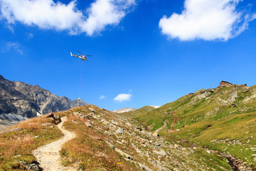 Transport helicopter flying with supplies and mountain panorama with alpine hut in Hohe Tauern Alps, Austria