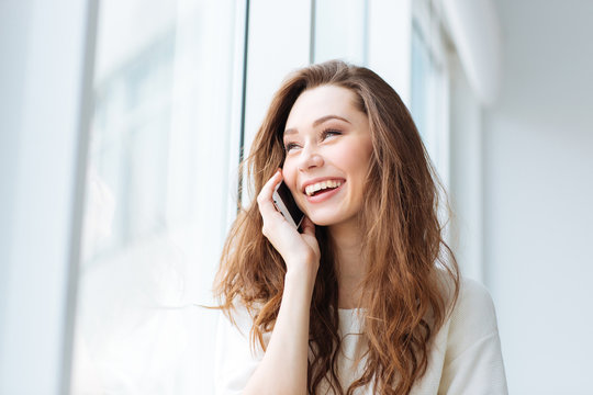 Woman talking on the phone and looking at window