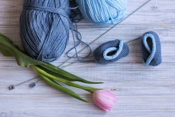 booties for newborns, spokes, two skeins of yarn, pink tulips lie on a blue background