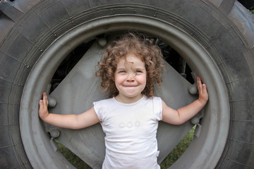 Little curly girl of European appearance sits in a large wheel t