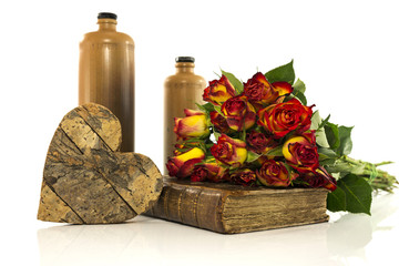 stone bottle with old book and red roses
