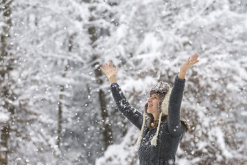 Happy young woman celebrating winter by raising her arms up in t