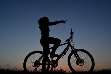 Mountain biker girl silhouette in beautiful sunset