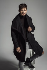 Portrait of handsome model in black long coat