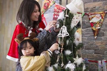 ツリーを飾り付けるお母さんと娘
