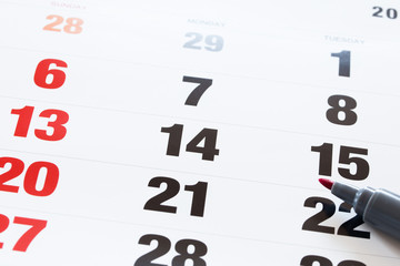 Setting an important date on a calendar with a red pencil markin