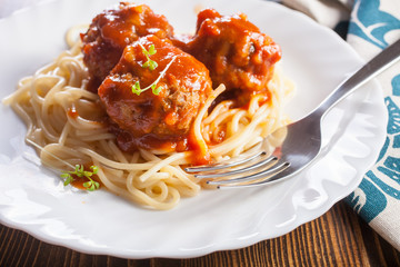 meatballs in tomato sauce from spaghetti in a plate on a table, selective focus
