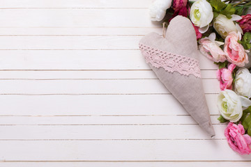 Pink and white flowers and decorative heart  on white wooden bac