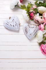 Flowers in pink colors and decorative hearts  on white wooden ba