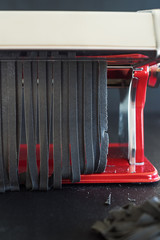 Squid ink tagliatelle being cutted with pasta machine