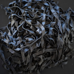Pile of fresh homemade squid ink tagliatelle. Selective focus