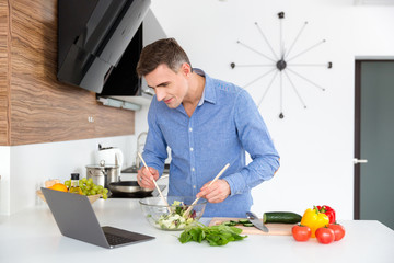 Attractive male looking on screen of laptop and cooking