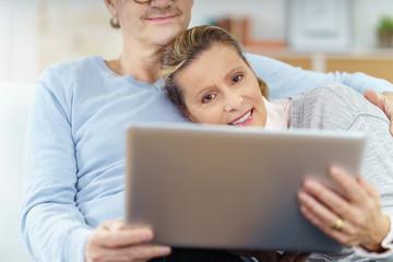 älteres paar liegt auf dem sofa und schaut auf laptop