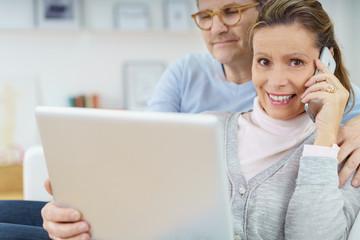 älters ehepaar zuhause mit laptop und mobiltelefon