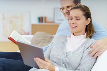frau zeigt ihrem mann etwas auf dem tablet