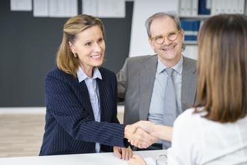 beraterin gibt einer kunden die hand nach dem erfolgreichen gespräch
