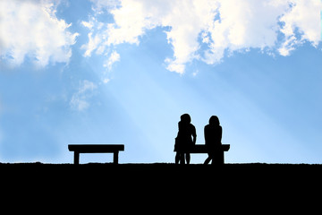 The silhouette of two friend sitting together with light through clouds background, concept of real friend needed, being friend