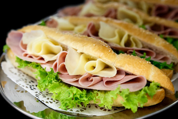 Yellow sliced cheese, ham and salad white  baguettes on doily and stainless steel tray. Black background.
