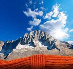 In de dag Alpinisme Mountain Climbing Concept / Red climbing rope with a mountain peak on background with blue sky and sun rays. Mountain climbing concept
