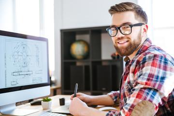 Happy designer drawing blueprint on computer using pen tablet