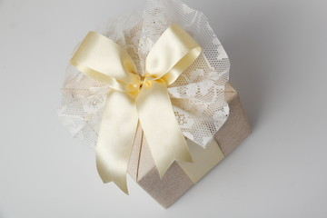 Beautifully wrapped gift./Beautiful gift box with packing beige paper, gold ribbon and lace.