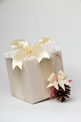 Beautifully wrapped gift with a pine cone./Beautiful gift box with packing beige paper, gold ribbon and lace. Pine cone.