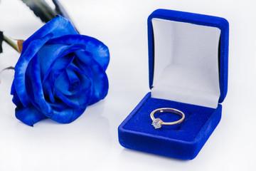 Golden engagement ring in a blue velvet box and blue rose