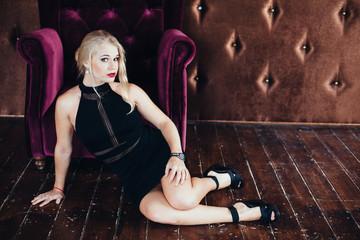 elegant fashionable woman in black dress posing luxury interior