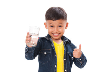Happy boy holding glass of water and showing thump up on white background