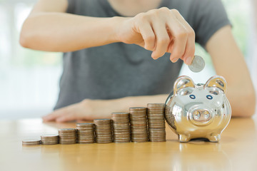 saving money-young woman putting a coin into a money-box-close u