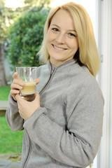 Frau trinkt Cappuccino, Latte Macchiato oder Kaffee mit Milchschaum
