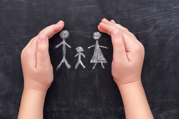 Child hands protecting family drawn on chalkboard