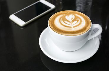 Cups of latte art coffee on black table
