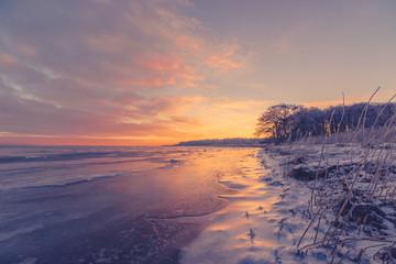 Beautiful sunrise at a frozen sea shore